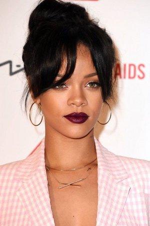 Η μελαμψή Rihanna δείχνει εντυπωσιακή με ένα σκούρο μπορντό-μοβ κραγιόν. Τα μάτια της έχουν τονιστεί με καφέ μολύβι εσωτερικά του βλεφάρου, μια έντονη γραμ